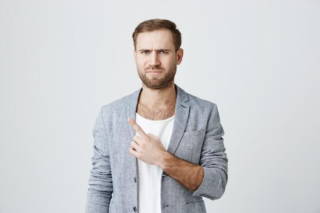 Cético homem barbudo descontente, apontando o canto superior esquerdo