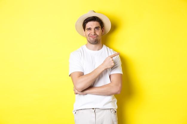 Cético turista masculino reclamando, apontando o dedo certo para algo ruim ou coxo, parado sem graça contra um fundo amarelo.