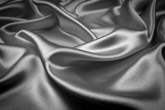 Cetim luxuoso da textura de seda preta para o fundo abstrato. tom escuro de tecido