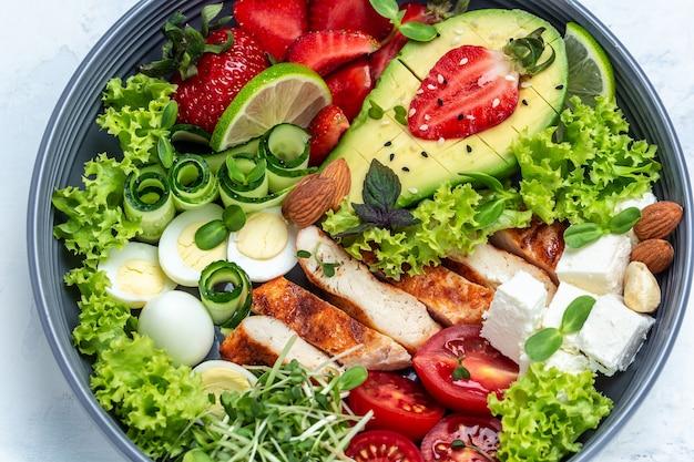 Ceto saudável, menu de almoço cetogênico com carnes de frango grelhadas, abacate, queijo feta, ovos de codorna, morangos, nozes e alface. peito de frango assado, filé e salada de legumes fresca, vista de cima.