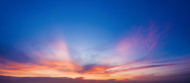Céu azul brilhante com nuvens roxas ao pôr do sol.