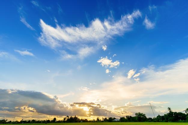 Céu azul brilhante e dramático ao pôr do sol no campo ou na paisagem de nuvens coloridas da praia