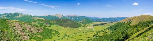 Céu azul claro sobre vale verde e paisagem de planalto