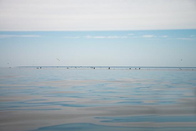 Céu azul com nuvens e reflexo do sol na água com lugar para o seu texto. nuvens espantosas, névoa no céu
