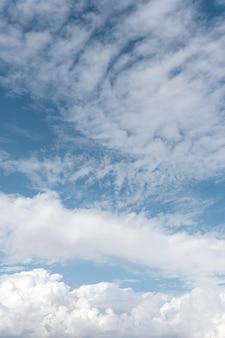 Céu azul com nuvens ventosas tiro vertical