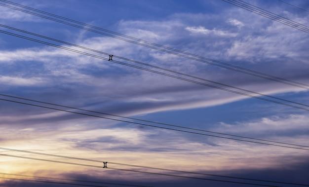 Céu azul dramático da noite acima do fio de alta tensão