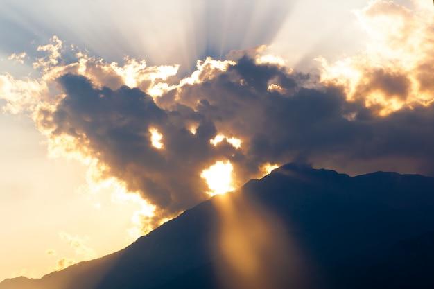 Céu azul e alaranjado do por do sol com raios do sol.