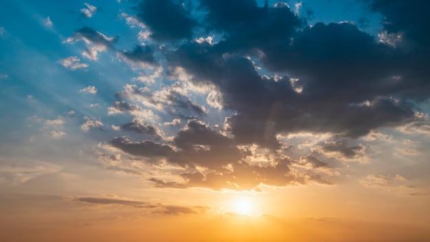 Céu azul e laranja por do sol com raios de sol. paisagem natural para segundo plano.