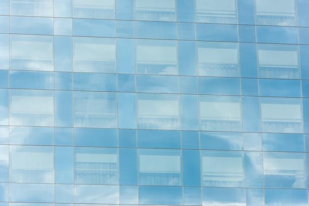 Céu azul e nuvens refletidas nas janelas do prédio de escritórios moderno