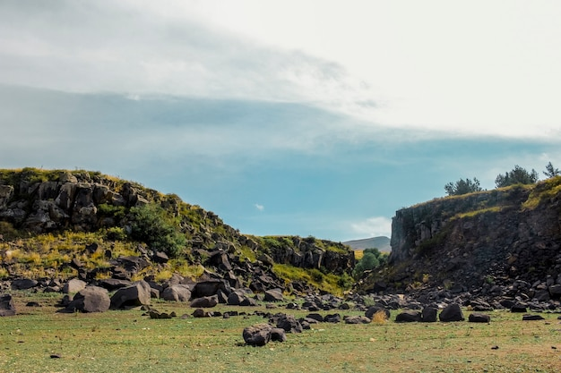 Céu azul e nuvens sobre paisagem rochosa filmadas de um ângulo baixo