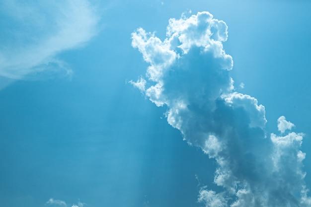 Céu azul ensolarado com nuvens suaves e sol brilhante contra o primeiro plano de árvores verdes