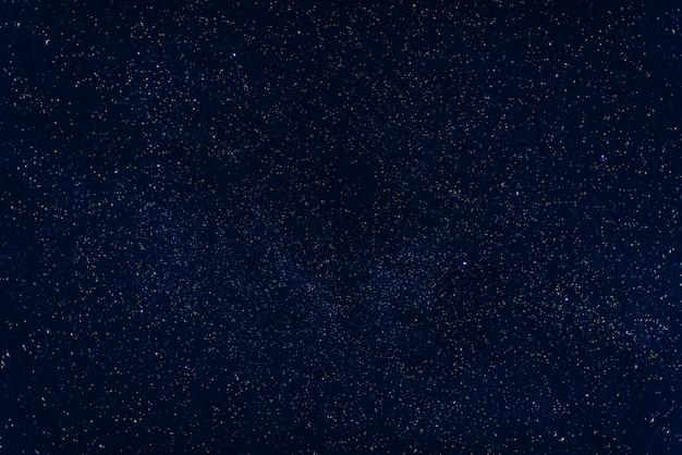 Céu azul escuro com via láctea e nebulosas