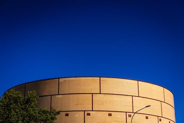Céu azul intenso em uma área industrial com uma construção de tijolo com formas redondas.