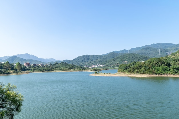 Céu azul, montanhas e árvores verdes cercam o lago