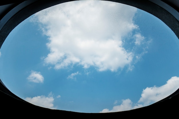 Céu azul nublado por uma janela