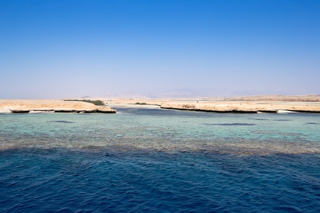 Céu azul sobre mar calmo com reflexo da luz do sol