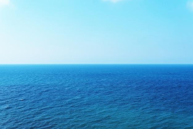 Céu azul sobre o mar com reflexão. mar calmo de textura de harmonia para a água.