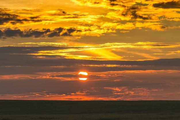 Céu cênico durante o pôr do sol sobre uma faixa escura de campo_