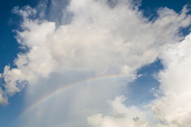 Céu claro com nuvens e rianbow, fundo azul