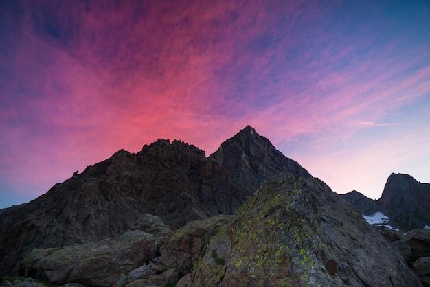 Céu colorido além do pico da montanha rochosa nos alpes italianos ao entardecer
