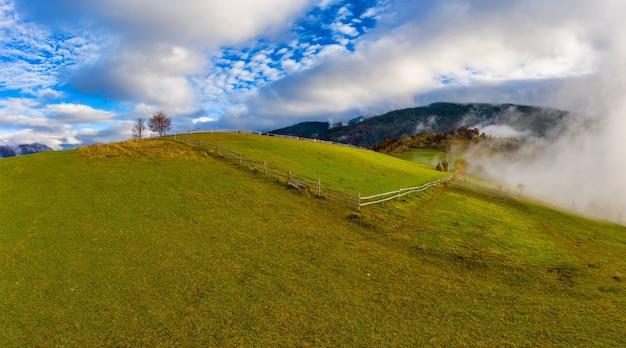 Céu com uma camada branca e fofa de nuvens sobre colinas verdes de outono