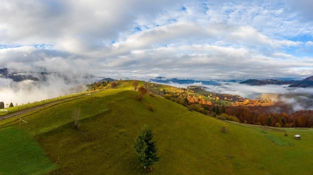 Céu com uma camada de nuvens brancas e fofas sobre colinas verdes de outono