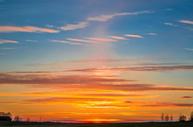 Céu da noite ao pôr do sol e silhueta de uma paisagem de vila rural.