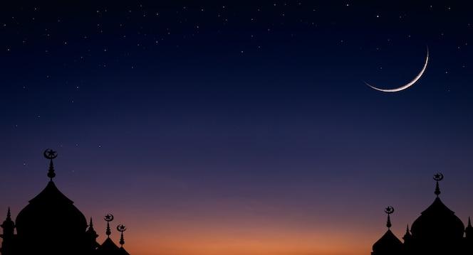Céu de lua crescente no crepúsculo azul escuro sobre a silhueta da mesquita em cúpula