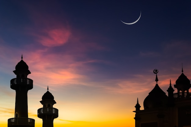 Céu de lua crescente no crepúsculo azul escuro sobre a silhueta da mesquita islâmica