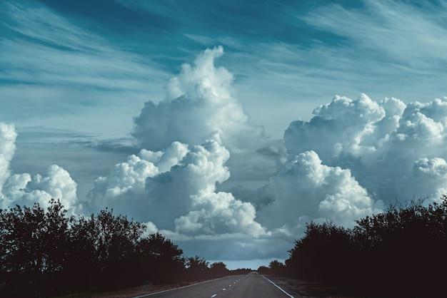 Céu deslumbrante com grandes nuvens escuras e paisagem da estrada