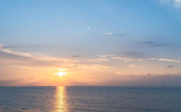 Céu do pôr do sol vertical sobre o mar à noite com luz do sol colorida