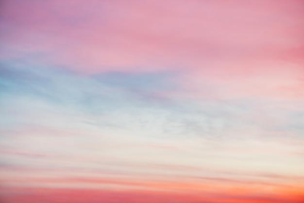 Céu do sol com nuvens de luz laranja rosa. gradiente colorido céu azul suave. fundo natural do nascer do sol. céu incrível de manhã. um pouco nublado noite atmosfera. clima maravilhoso ao amanhecer.