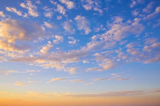 Céu do sol com nuvens douradas e azuis
