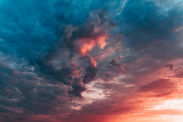 Céu do sol dramático com nuvens multicoloridas