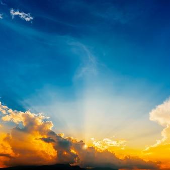Céu do sol e nuvens com raios de sol