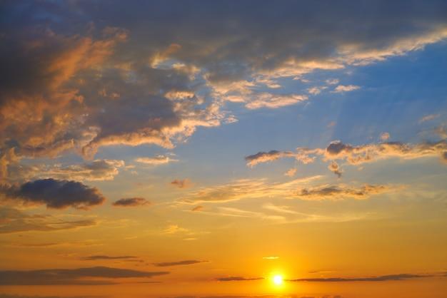 Céu do sol em laranja e azul