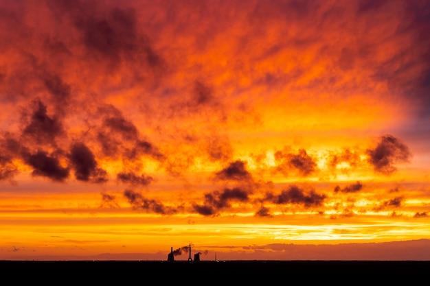 Céu do sol laranja ardente. sol vermelho do nascer do sol sobre a paisagem urbana. por do sol amarelo vermelho dramático sobre a indústria da cidade. nuvens azuis vermelhas ao pôr do sol à noite. lindo céu com nuvens.
