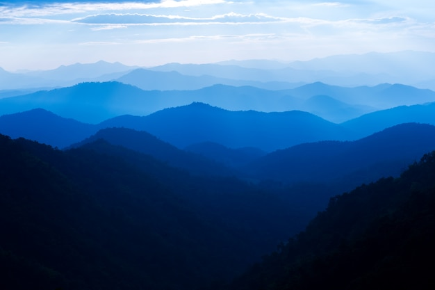 Céu do sol majestoso sobre paisagem de camadas de montanhas azuis