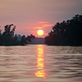 Céu do sol no lago das madeiras, ontário