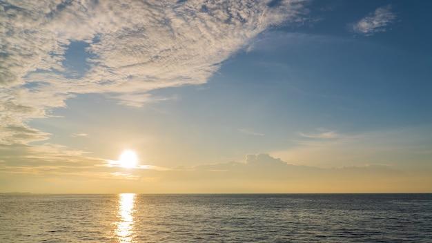 Céu do sol sobre o mar à noite com nuvens coloridas de luz solar.