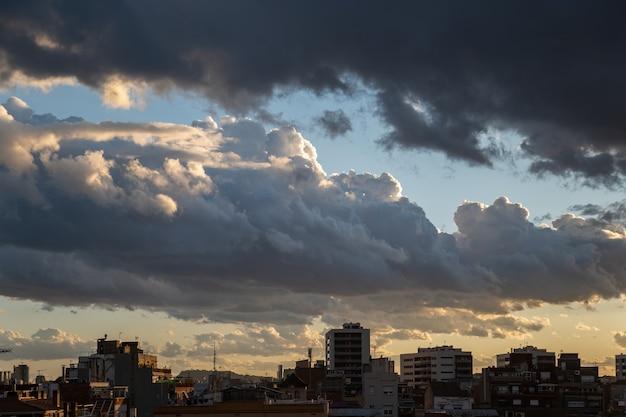 Céu dramático ao entardecer do sol sobre a cidade com nuvens pesadas.