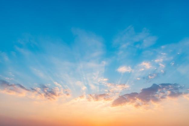 Céu dramático bonito do por do sol com as nuvens coloridas alaranjadas e azuis.
