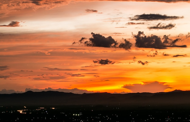 Céu dramático colorido com a nuvem no por do sol.