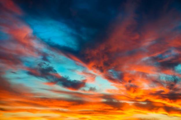 Céu dramático colorido de laranja e azul com nuvens para o fundo abstrato