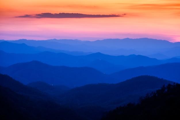 Céu dramático pôr do sol e nascer do sol e nuvens sobre camadas de montanhas azuis