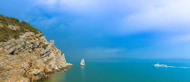 Céu dramático sobre a costa rochosa e a rocha parus na costa do mar negro