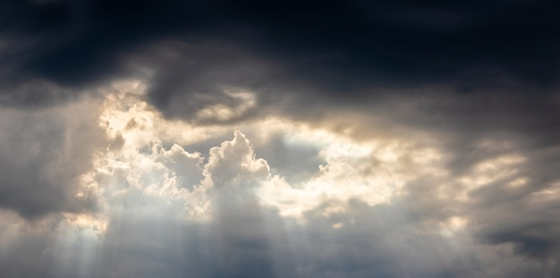 Céu escuro e tempestuoso, a luz do sol penetra através de nuvens negras de tempestade