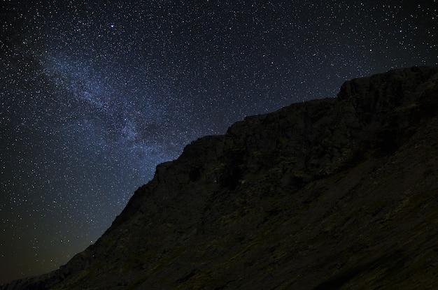 Céu estrelado à noite. a via láctea no fundo de uma cordilheira.