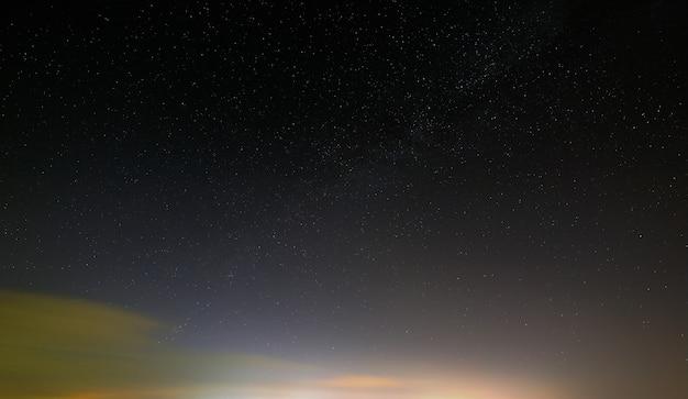 Céu estrelado à noite com nuvens após o pôr do sol.