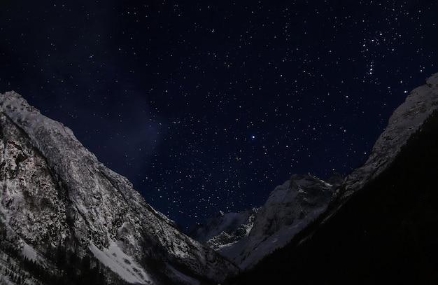 Céu estrelado à noite nas constelações de montanhas nevadas sirius e orion